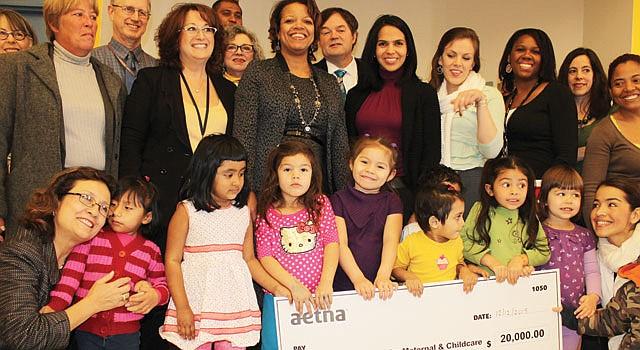 FELICES. María Gómez ( abajo izq.), CEO de Mary's Center, celebra, el 12, acompañada de su comunidad y de representantes de Aetna.