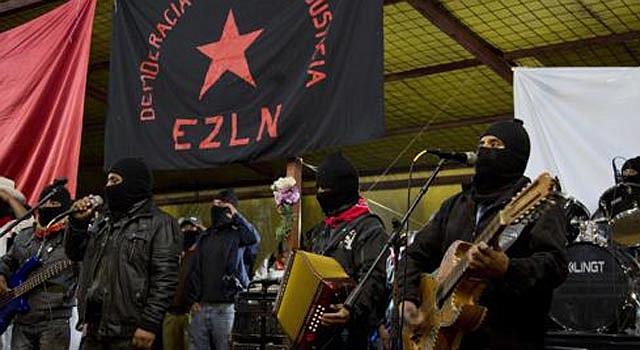 Integrantes del Ejército Zapatista de Liberación Nacional cantan el himno de su organización durante un evento en el que se conmemoró el aniversario 20 del alzamiento armado.