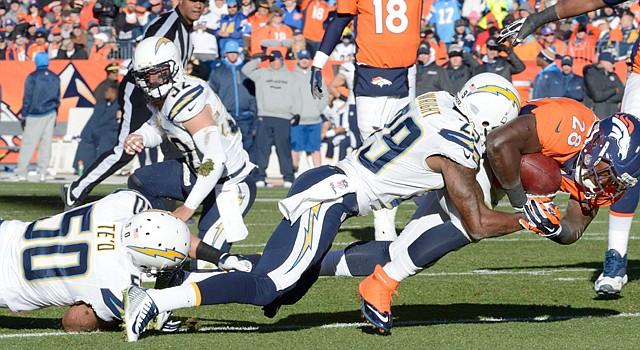 El corridor Montee Ball (der.) de los Broncos de Denver es bloqueado pro Shareece Wright de los Chargers de San diego durante el partido del playoff divisional de la Conferencia Americana el domingo 12 de enero de 2014 en el   Sports Authority Field en Mile High, Denver, Colorado.
