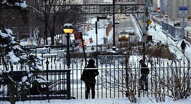 Peatones recorren aceras cubiertas de nieve y el tráfico cruza el puente de Brooklyn, miércoles 22 de enero de 2014 en Nueva York. Una tormenta invernal con nieve y mucho frío azota el noreste de Estados Unidos