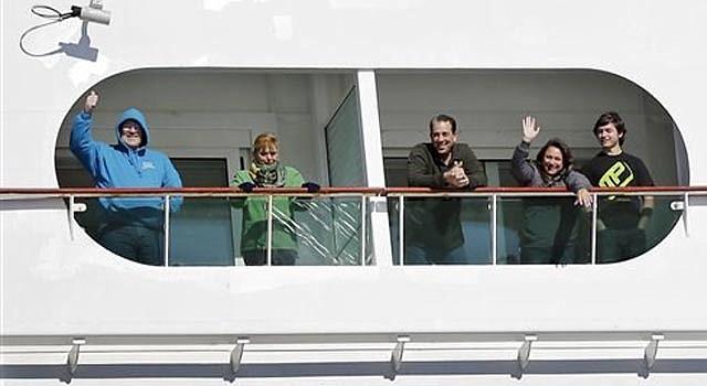 Varios pasajeros saludan desde el crucero Explorer of the Seas a su llegada a puerto en Bayonne, Nueva Jersey, el miércoles 29 de enero de 2014. La cifra de pasajeros y tripulantes que enfermaron en el viaje ha aumentado a casi 700.