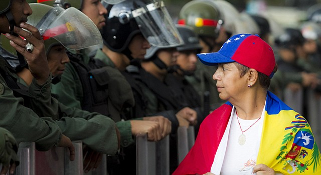 Una mujer camina frente a miembros de la Guardia Nacional Bolivariana (GNB) durante una protesta contra el gobierno de Venezuela el lunes 17 de febrero de 2014, en el sector Altamira de Caracas (Venezuela). El Gobierno de Nicolás Maduro lanzó duras acusaciones a Estados Unidos inculpándole de estar detrás de la violencia que ha empañado las marchas pacíficas en Venezuela, mientras el dirigente opositor Leopoldo López ratificaba su intención de marchar el martes al Ministerio del Interior.