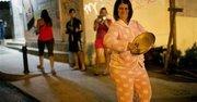 Una mujer en pijama se une a los cacerolazos en protesta contra el gobierno venezolano, en el vecindario de Altamira, Caracas, el viernes 21 de febrero de 2014. Se prevé que las movilizaciones sigan el fin de semana. (Foto AP/Rodrigo Abd)