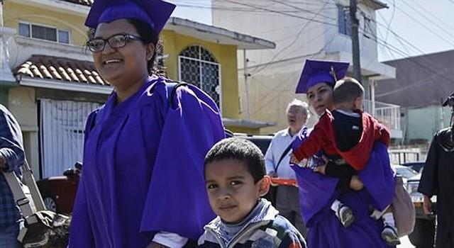 Angelica López toma las manos de sus hijos Osmar y Ashley al marchar hacia la frontera con EEUU en Tijuana, México, lunes 10 de marzo de 2014. (AP Foto/Lenny Ignelzi)