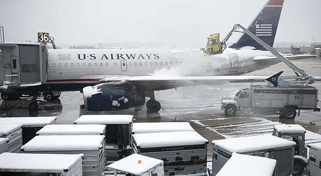 Trabajadores limpian de nieve un avión en el aeropuerto Reagan en Arlington (Estados Unidos) hoy, lunes 17 de marzo de 2014. EFE/Shawn Thew