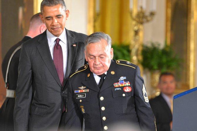 El presidente ayudando a subir al podium a José Rodela, el tercer veterano sobreviviente de los 24 que fueron reconocidos el martes 18 en la Casa Blanca.