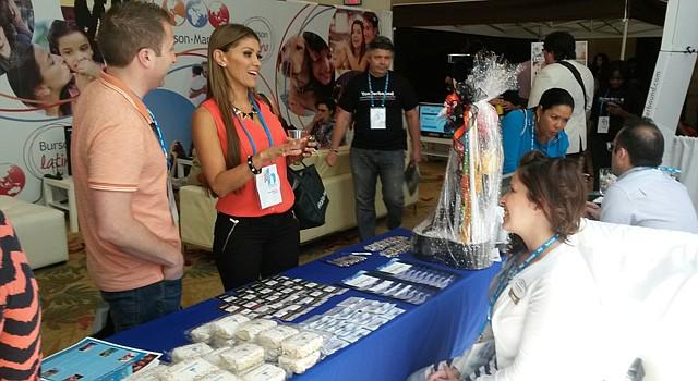 Claudia De la Torre (der.), Gerente de Eventos Especiales de Walt Disney World, habla con dos visitantes a la sección de esa empresa en Hispanicize, el jueves 3 de abril de 2014 en el Hotel Intercontinental de Miami, Florida.