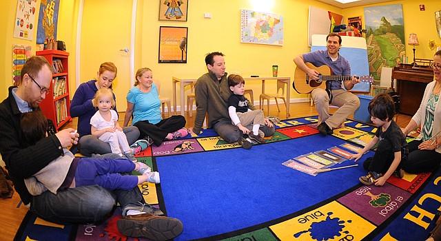 """El director musical de Isabella & Ferdinand, Francisco Revert, toca la guitarra mientras la profesora Jessica Espinosa (der.) canta junto a los padres y niños en la clase """"Baby Barcelona"""" del sábado 15 de marzo de 2014."""