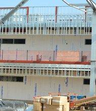Un trabajador recibe la estructura metálica para depositarla sobre el segundo piso del nuevo edificio, integrado por 11 aulas escolares.