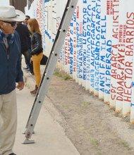 Un exbracero observa los nombres de inmigrantes deportados inscritos en el muro metálico en Playas de Tijuana.