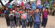 Los niños de la aldea Tamayupo en Honduras celebran recibir sus mochilas con útiles escolares el 5 de enero de 2014 gracias a la Glo Foundation, una iniciativa de la joven hondureña, Gloria Sierra, quien vive en Maryand.