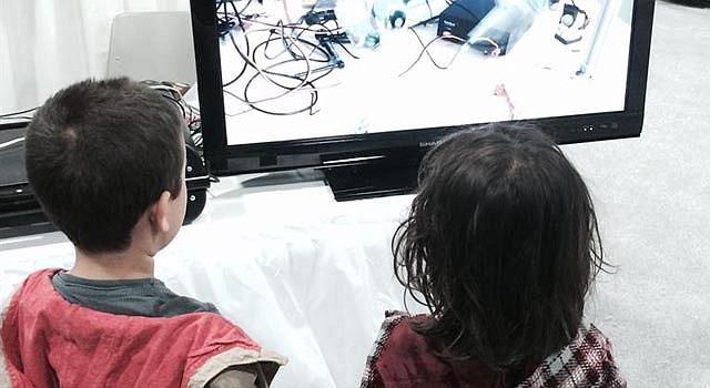 Dos niños observan un pantalla de televisión el sábado 26 de abril de 2014, durante el Festival Estadounidense de Ciencia e Ingeniería que congrega en el Centro de Convenciones de Washington (EE.UU.) a 1.200 expositores, entre ellos 150 grandes compañías como Microsoft, Intel y el contratista de defensa Lockheed Martin, principal patrocinador del evento.