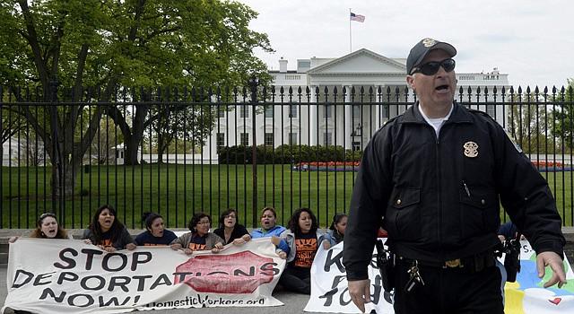 """Varias personas se manifiestan mostrando pancartas en las que se puede leer """"Mantener las familias juntas"""" y """"Detención de las deportaciones ahora"""" en contra de las deportaciones, detrás de un policía, a las afueras de la Casa Blanca en Washington DC, Estados Unidos el lunes 28 de abril."""