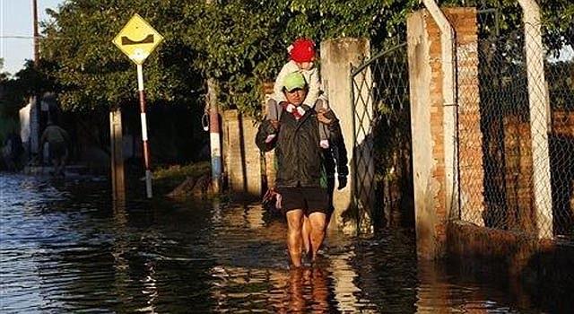 Oscar Caballero carga a su hija Nadia hacia la escuela en medio de una calle inundada en el vecindario de Tacumbu en Asunción, Paraguay, el martes 3 de junio de 2014. Más de 75.000 familias de zonas bajas de la capital y pueblos ubicados a orillas del río Paraguay abandonaron sus viviendas debido a las inundaciones producidas por intensas lluvias y el crecimiento cíclico del río, informaron las autoridades. (AP foto/Jorge Saenz)