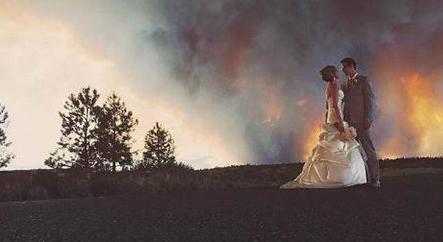 Los novios Michael Wolber y April Hartley posan para un retrato cerca de Bend, Oregon, con un incendio forestal como fondo el día de su boda en una fotografía del sábado 7 de junio de 2014 proporcionada por Josh Newton. La ceremonia de la boda se acortó por el incendio y la fiesta tuvo que ser realizada en otro lugar. (Foto AP/Josh Newton)