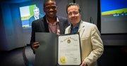 Jonathan J. Green (izq.) hace entrega al editor de El Tiempo Latino, Alberto Avendaño, de un reconocimiento oficial del Gobernador de Maryland, Martin O'Malley, a 23 años de servicio comunitario de la publicación, durante el evento del Mundial de Fútbol Brasil 2014 en el auditorio del Washington Post, el 9 de julio.