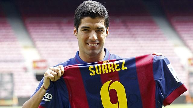 El delantero uruguayo Luis Suárez, que ha sido presentado el martes 19 oficialmente como nuevo jugador azulgrana, cinco semanas después de fichar por el Barcelona y tras jugar el lunes sus primeros minutos en el Trofeo Joan Gamper, muestra su nueva camiseta en el césped del Camp Nou.