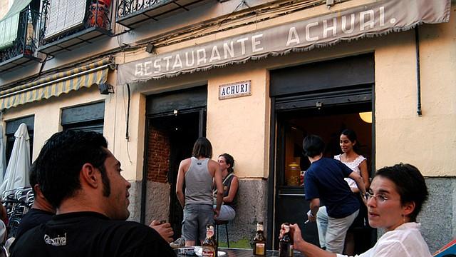 Varios jóvenes hispanohablantes platican en la terraza de un restaurante. Los hispanohablantes tienden a expresarse de manera más positiva.