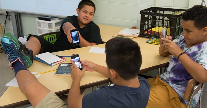 Angel Zelaya, Jimmy Benitez-Calderon and Devin Downer work together using personal smartphone cameras during sixth grade. (Kate Patterson/For The Washington Post)