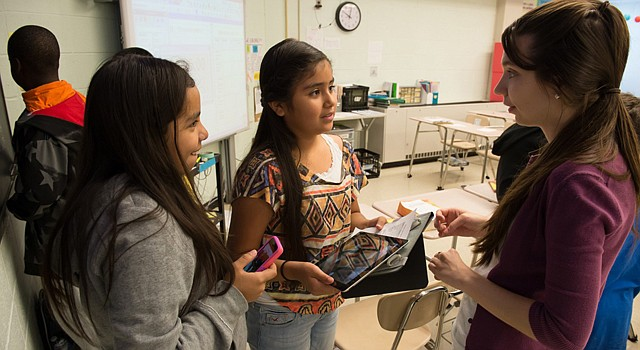 Katie Martinez, left, and Genesis Delcid talk with their teacher, Ginger Berry, about their project which requires them to use their personal smartphone cameras during Project Success class at Argyle Middle School. (Kate Patterson/For The Washington Post)
