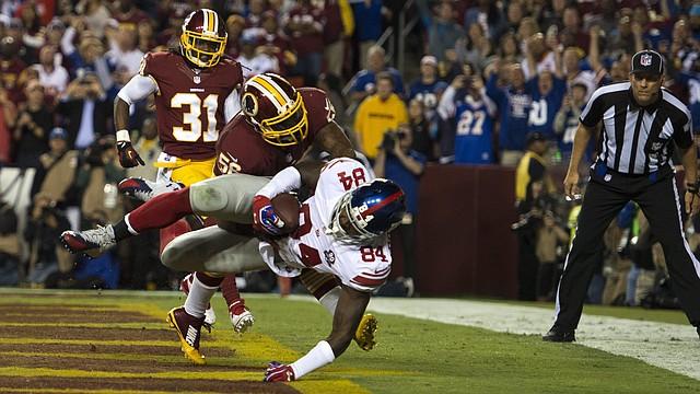 Larry Donnell (d) de Giants atrapa una bola ante Perry Riley (c) de Redskins el jueves 25 de septiembre de 2014, durante un juego de la NFL en el Fedex Field de Landover, Maryland