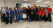 La alcaldesa de Baltimore, Rawlings-Blake (centro) junto a El Devarie, CEO de EMD Sales, y parte de los empleados de la compañía de distribución de productos alimenticios, el 23 de septiembre de 2014, en Baltimore, Maryland.