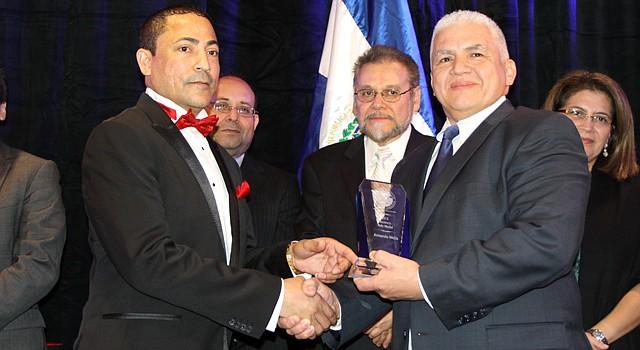 Henry Bonilla (izq.) presidente de The Salvadoran American Chamber of Commerce premia al empresario Armando Mejía en una gala en 2013. Al centro, el empresario de la industria de la tecnología Charles Vela.