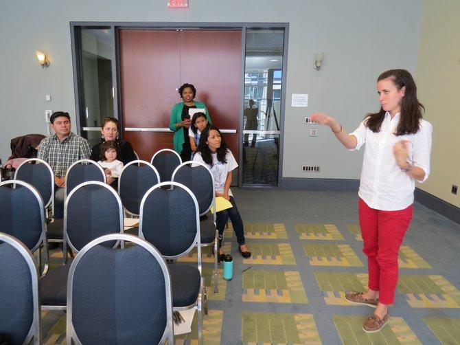 Ali Skelton (der.), del Latino Student Fund, explica sobre el Programa Acceso a asistentes a los talleres informativos en el marco de la Feria de Escuelas Privadas en Washington, DC. Atrás se observa de pie a Xiomara Hall, directora de admisión y asistencia financiera de la St. Patrick's Episcopal Day School.