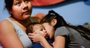 Rosa Pelaez, 32, holds her youngest child, Sebastian, 2 months, as her daughter, Briana Flores, 6, gives a kiss to her brother. (Sarah L. Voisin/The Washington Post)