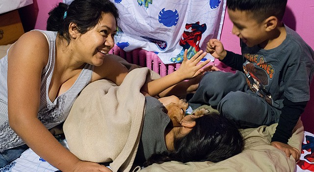 Rosa Pelaez, 32, left, laughs with two of her children, Briana, 6, center, and Edwin, 5, and the family Chihuahua as she puts them to bed. (Sarah L. Voisin/The Washington Post)