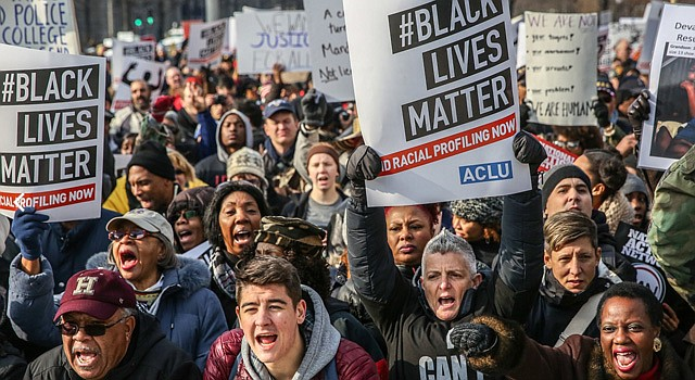 """Demonstrators listen to speeches at Freedom Plaza at the start of the """"Justice for All"""" march in the District."""