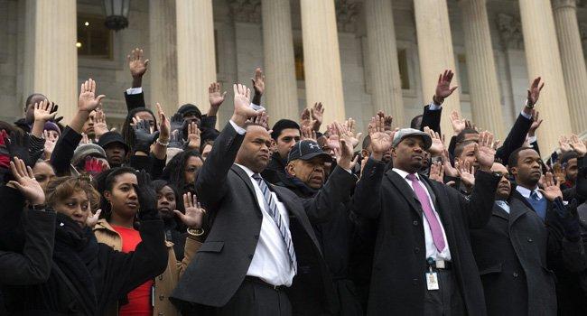 Los senadores estadounidenses Marc Veasey (4i) y Elijah Cummings (5i) levantan sus manos en las escaleras Este del Capitolio en Washington DC (EE.UU.) hoy, jueves 11 de diciembre de 2014, durante una protesta contra la decisión del gran jurado para no procesar a policías en los casos de las muertes de Mike Brown y Eric Garner.