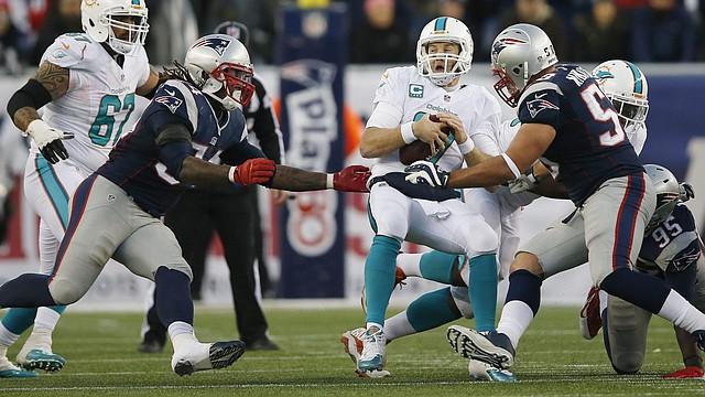 El jugador de New England Patriots Dont'a Hightower (izq.) en acción contra Rob Ninkovich y Ryan Tannehill (centro) del Miami Dolphin durante el partido en el Gillette Stadium de Foxborough, Massachusetts, el 14 de diciembre de 2014.