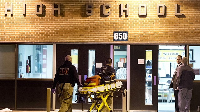 Officials enter Frederick High School, Wednesday. Police and school officials say students were shot outside the public high school while a basketball game was being played inside.