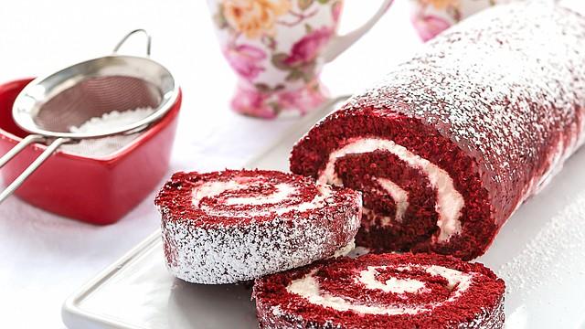"""Este tipo de pasteles enrollados se conocen en mi país, Venezuela, como Brazo gitano. Se consiguen con muchos tipos de rellenos como chocolate, mermeladas de frutas, dulce de leche, etc… Esta receta que les traigo es una versión diferente del muy popular pastel """"Red Velvet"""". Una verdadera delicia."""