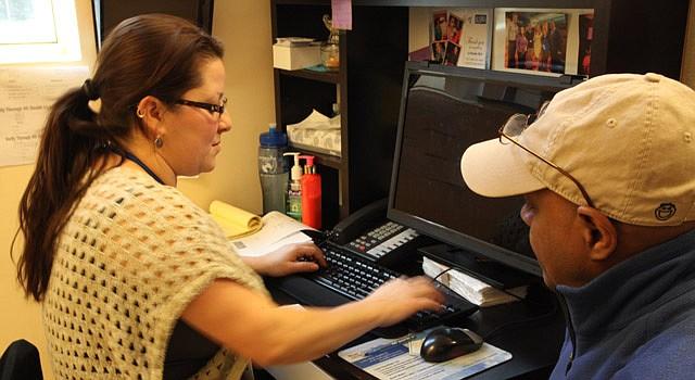 AYUDA. Rosa Martínez (izq.) orienta a un residente de DC a inscribirse, el sábado 7 de febrero en La Clínica del Pueblo.