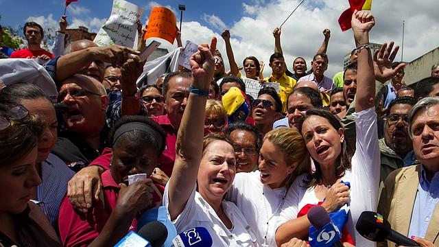 """La esposa del alcalde mayor de Caracas, Antonio Ledezma, Mitzy Capriles (c-i), acompañada de la esposa del líder político venezolano encarcelado Leopoldo López, Lilian Tintori (c), y de la exdiputada de la Asamblea Nacional (AN) María Corina Machado (c-d), asiste hoy, viernes 20 de febrero de 2015, a una manifestación para rechazar la detención de Ledezma, en la capital venezolana. El Ministerio Público de Venezuela (MP) informó hoy que imputará a Ledezma, detenido el jueves por agentes de inteligencia, por su supuesta vinculación con una conspiración para """"organizar y ejecutar"""" actos violentos contra el Gobierno de Nicolás Maduro."""