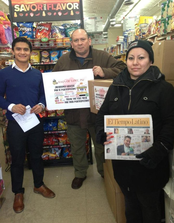 (de izq. a der.) Celso Pastran de EMD Sales y Luis Torrico de El Tiempo Latino junto a una señora que recibió una caja de productos el 28 de febrero durante el programa Bolsas de Amor en International progreso, el supermercado de la Georgia Avenue en washington, DC.