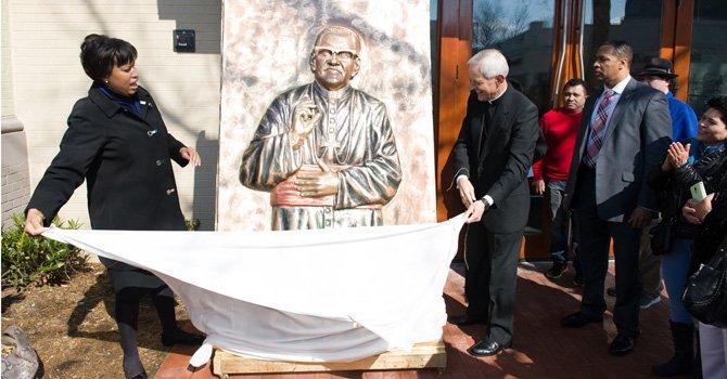 La alcaldesa de Washington, DC, Muriel Bowser desvela una imagen del arzobispo salvadoreño Monseñor Óscar Romero, el sábado 21 de marzo de 2015, durante a dedicatoria de un edificio de la Mount Pleasant, en DC, al arzobispo.