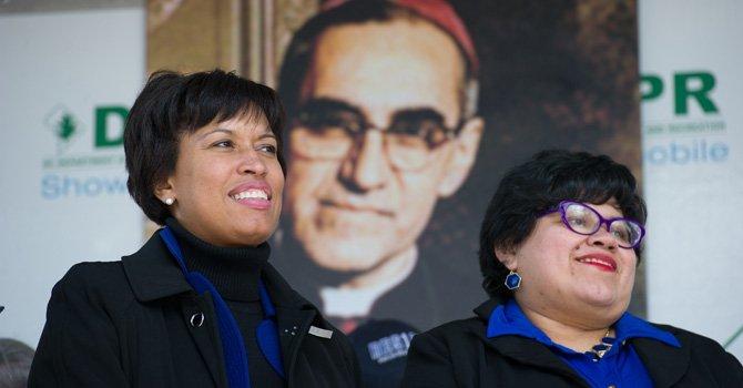 La alcaldesa de DC, Muriel Bowser (izq.) junto a la directora de la Oficina de la Alcaldesa para Asuntos Latinos (OLA), Jackie Reyes, el sábado 21 de marzo, durante la dedicatoria de un edificio de la Mount Pleasant al arzobispo salvadoreño Oscar Romero.
