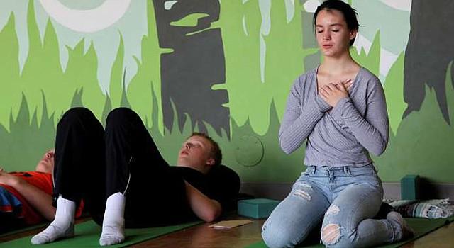 En esta fotografía de archivo del 1 de octubre de 2014, Nora Pearson, derecha, practica concentración en la respiración durante la clase de atención plena en la secundaria Wilson en Portland, Oregon.