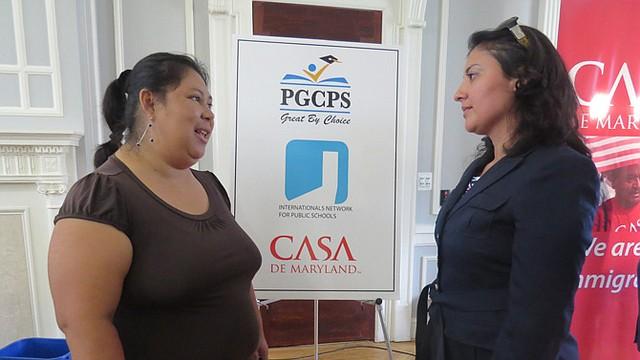 Lydia Rivas (izq.), con dos hijos, dijo que las escuelas de Langley Park estarán más cerca de su vecindario. A la der., Maritza González, asistenta al superintendente de Educación sobre Diversidad en las Escuelas Públicas del Condado de Prince George's durante un anuncio en julio de 2014 sobre el establecimiento de dos nuevos centros escolares.