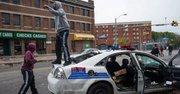 Personas gritan sobre un vehículo de la policía abandonado que fue atacado durante protestas luego del funeral de Freddie Gray hoy, lunes 27 de abril de 2015, en Baltimore
