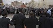 Una barrera de la policía bloquea una calle de Baltimore a manifestantes durante protestas por la muerte de Freddie Gray hoy, lunes 27 de abril de 2015
