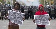"""Jóvenes sostienen carteles que dicen """"Detengan el asesinato por policías"""" durante protestas después del funeral Freddie Gray hoy, lunes 27 de abril de 2015, en Baltimore"""