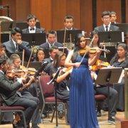 Una joven interpreta un solo de violín durante el concierto de la Orquesta Don Bosco en el Kennedy Center.