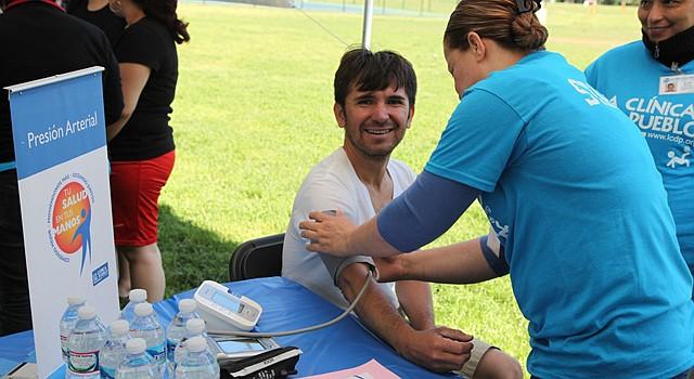 EVENTO. Carlos Castillo con voluntarios de La Clínica del Pueblo que le miden la presión arterial en 2014.