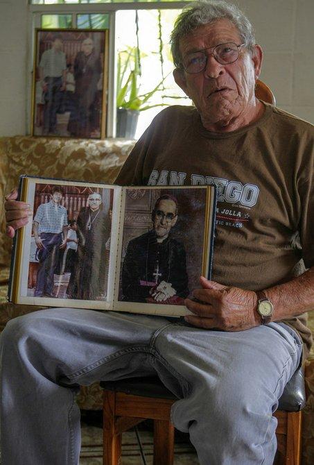 """Fotografía fechada el 22 de mayo de 2015 que muestra a Jorge Alberto Hernández, chófer de Romero cuando fue obispo de la diócesis de Santiago de María (Usulután), entre 1974 y 1977, mientras sostiene fotografías durante una entrevista en San Salvador (El Salvador). Defensores de derechos humanos y allegados a Romero dicen que el arzobispo, asesinado el 24 de marzo de 1980, era el """"ancla"""" que impedía a El Salvador zarpar a un viaje de sangre y dolor que le costaría la vida de unas 75.000 personas en 12 años de guerra civil."""