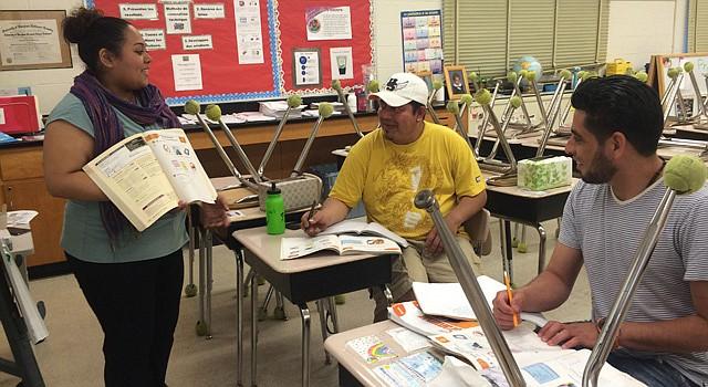 La maestra Sylvia Granados y dos de sus alumnos del curso de inglés para principiantes: Raúl Aguilar y Nolvin Guzmán, revisan la lección del dia en una escuela pública del condado de Montgomery, Maryland. Es el Language Outreach Program, una iniciativa de la organización sin fines de lucro Community Ministries de Rockville.