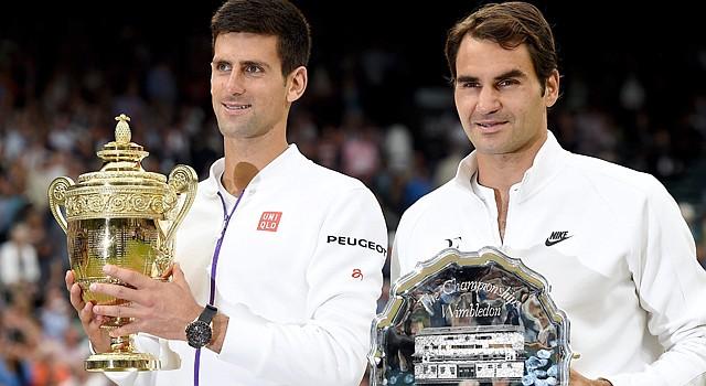 Novak Djokovic (izq.) de Serbia pisa con su trofeo luego de derrotar al suizo Roger Federer (der.) en la final de Wimbledon el domingo 12 de julio de 2015.